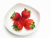 Fresh strawberries. Four freshly picked strawberries served on a white plate Royalty Free Stock Photography