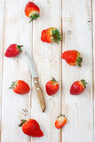 Fresh strawberries. With knife on white desk Stock Images