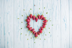 Fresh strawberries array heart shape on old wooden background royalty free stock photos