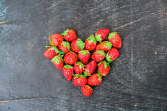 Fresh strawberries array heart shape on old wooden background Royalty Free Stock Photo