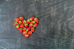Fresh strawberries array heart shape on old wooden background Royalty Free Stock Image