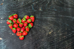Fresh strawberries array heart shape on old wooden background Royalty Free Stock Images