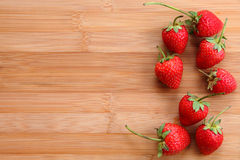 Fresh strawberries on bamboo table. Royalty Free Stock Images