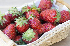 Fresh strawberries in basket. Fresh strawberries with green tails wickerwork basket with white napkin royalty free stock image