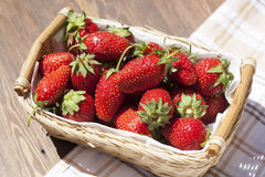 Fresh strawberries with basket with white napkin. Fresh strawberries with green tails wickerwork basket with white napkin royalty free stock photo