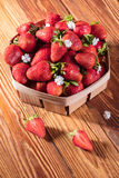 Fresh strawberries in a basket. On wooden background stock photography