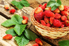 Fresh strawberries in a basket on wooden table with green laves Stock Photo