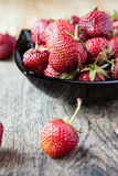 Fresh strawberries in a black bowl on the table Stock Photos