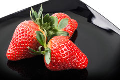 Fresh strawberries on black saucer Stock Images