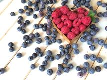 Raspberries and blueberries on wood. Red raspberries in heart shape wooden basket with fresh blueberries scattered on white retro wood table Royalty Free Stock Images