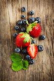 Fresh strawberries and blueberries on wooden background Stock Photos