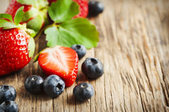 Fresh strawberries and blueberries on wooden background Royalty Free Stock Image