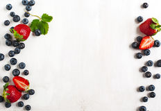 Fresh strawberries and blueberries on wooden background. Fresh strawberries and blueberries on white wooden background Royalty Free Stock Photography