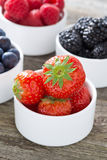 Fresh strawberries in a bowl and berries, closeup, vertical Royalty Free Stock Photo