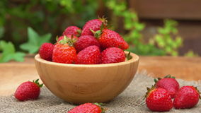 Fresh strawberries in a bowl on a table stock footage