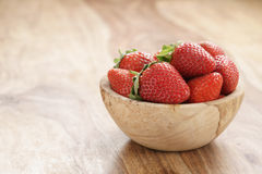 Fresh strawberries in bowl on wood table Stock Photography