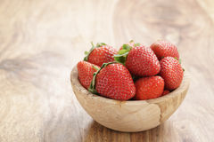 Fresh strawberries in bowl on wood table Royalty Free Stock Photography