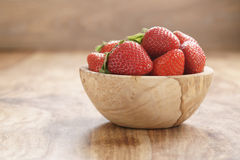 Fresh strawberries in bowl on wood table Stock Photo