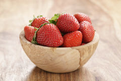 Fresh strawberries in bowl on wood table Royalty Free Stock Photo