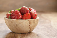 Fresh strawberries in bowl on wood table Royalty Free Stock Image