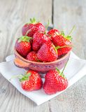 Fresh strawberries in the bowl on the wooden table Stock Photo