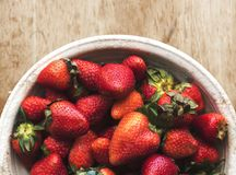 Fresh strawberries in a bowl on wooden table stock photography