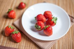 Fresh strawberries in a bowl on wooden table stock photo