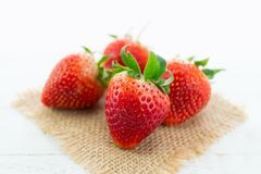 Fresh strawberries on burlap and white wood background with sele. Ctive focus point Royalty Free Stock Photography