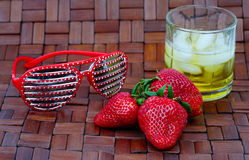 Fresh strawberries, cocktail and red eyeglasses on wooden backgr Stock Image