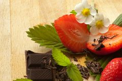 Fresh strawberries combined with dark chocolate. Sliced strawberries with leaves and flowers Stock Image