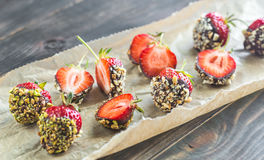 Fresh strawberries covered with dark chocolate and nuts. On the wooden background royalty free stock images