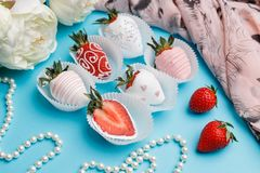 Fresh strawberries covered with white and pink chocolate, white flowers and pearl beads lie on a turquoise background stock image