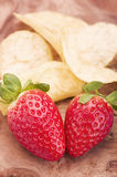 Fresh strawberries and crisps, chips on wooden background. Stock Photos