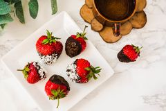 Fresh strawberries dipped in dark chocolate and coconut flakes w stock photography