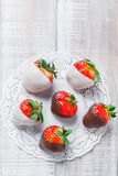 Fresh strawberries dipped in dark and white chocolate on light background close up. Delicious dessert and candy bar Stock Photos
