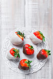 Fresh strawberries dipped in dark and white chocolate on light background close up. Delicious dessert and candy bar Stock Image