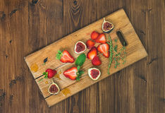 Fresh strawberries, figs, mint leaves, thyme and honey drops ob Stock Photography