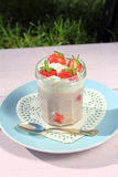 Fresh strawberries with fruit yoghurt and whipped cream on light pink wooden table Royalty Free Stock Photos