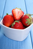 Fresh strawberries in glass bowl on blue boards, healthy dessert Stock Photos