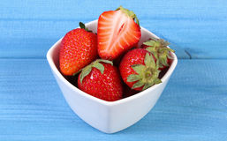 Fresh strawberries in glass bowl on blue boards, healthy dessert Royalty Free Stock Photography