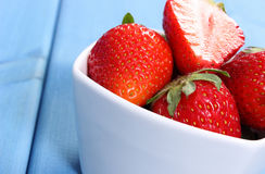 Fresh strawberries in glass bowl on blue boards, healthy dessert Stock Image