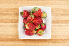 Fresh Strawberries. A group of fresh strawberries on a timber board Stock Photo