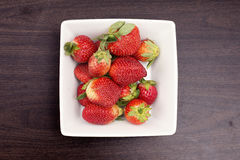 Fresh Strawberries. A group of fresh strawberries on a timber board Stock Photos