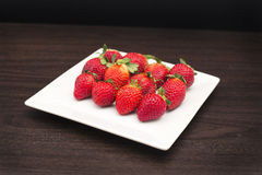 Fresh Strawberries. A group of fresh strawberries on a timber board Stock Image
