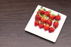 Fresh Strawberries. A group of fresh strawberries on a timber board Royalty Free Stock Image