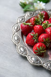 Fresh strawberries in heart shape plate. Fresh strawberries in vintage silver plate on wooden background, selective focus, close-up Royalty Free Stock Photos