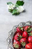 Fresh strawberries in heart shape plate. Fresh strawberries in vintage silver plate on wooden background, selective focus, close-up Royalty Free Stock Photo