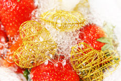 Fresh strawberries and hearts. Fresh strawberries with water bubbles on white Royalty Free Stock Image