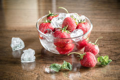 Fresh strawberries with ice cubes in the glass bowl Stock Photos