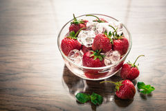Fresh strawberries with ice cubes in the glass bowl Stock Image